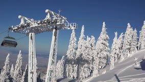 Ascensore di sci su cavo che porta i turisti, il paesaggio di inverno della montagna, il cielo blu e gli abeti coperti di neve archivi video
