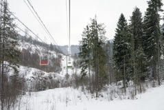 Ascensore di sci vuoto della sedia sulle montagne tristi Orario invernale Fotografia Stock