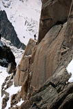 Ascent - Chamonix, France. A lone mountaineer prepares to ascend a rock face on the Aiguille du Midi in Chamonix, France royalty free stock photography