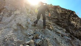 Ascent. Hiker reaching to summit. Girl climbs the mountain. Bright sunlight. Hiker reaching summit top after ascent. Hiking walking outdoors. Girl climbs the stock video