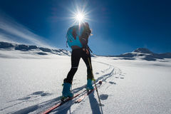Ascent with ski mountaineering and climbing skins for a single w. Oman in snow landscape Royalty Free Stock Images