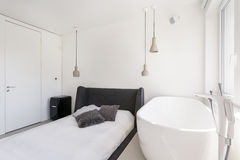 Ascetic bedroom with oval bathtub Royalty Free Stock Photos