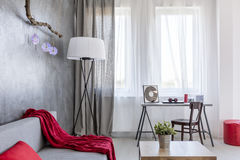 Ascetic home interior in grey. Style ascetic home interior in grey with , small table, desk, floor lamp and red details royalty free stock photos
