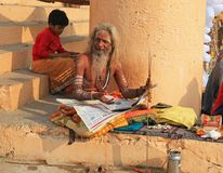 Ascetic Looks Up From Morning Newspaper, Varanasi, India. An ascetic looks up from the newspaper he was reading along the banks of the Ganges River in Varanasi stock images