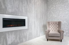 Ascetic room with armchair and fireplace. Ascetic room in grey color with armchair and fireplace royalty free stock photos