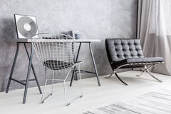 Ascetic but stylish decor of a modern apartment's office corner. Grey office room corner with a diamond chair next to a simple desk, and a leather lounge chair royalty free stock photos