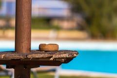 Aschenbecher auf einer Tabelle unter einem Sonnenschirm auf dem Strand Stockfotografie