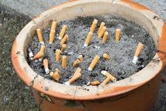 Aschenbecher im Freien mit Sand und Zigaretten Stockbilder