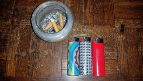 Aschenbecher mit drei mehrfarbigen Feuerzeugen Lizenzfreie Stockfotos