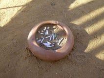 Aschenbecher mit Zigarettenkippen auf einem sandigen Strand Stockfoto