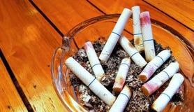 Aschenbecher und gestoßene heraus Zigaretten mit Lippenstift Stockfotografie
