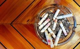 Aschenbecher und gestoßene heraus Zigaretten mit Lippenstift Lizenzfreies Stockfoto