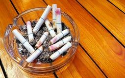 Aschenbecher und gestoßene heraus Zigaretten mit Lippenstift Stockbild