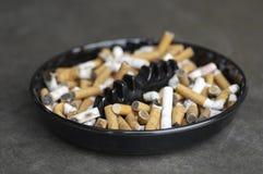 Aschenbecher voll von Zigarettenkippen Stockfotos