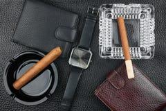 Aschenbecher zwei mit Zigarren, zwei Geldbeuteln und Uhren auf dem natürlichen L Lizenzfreie Stockfotos