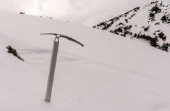 Ascia di ghiaccio su fondo di neve Immagini Stock Libere da Diritti