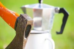 Ascia, macchinette del caffè del geyser e tazza Immagini Stock