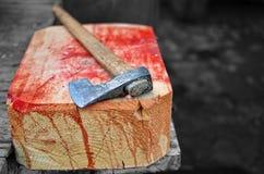 Ascia su un hogger sanguinoso di legno Fotografia Stock