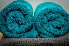 Asciugamani acciambellati del turchese situati su un asciugamano grigio fotografia stock libera da diritti