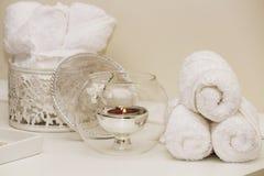 Asciugamani bianchi rotolati e candela rossa fotografia stock libera da diritti