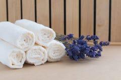 Asciugamani di bagno beige su fondo di legno e su un mazzo di lavanda secca Concetto della stazione termale fotografie stock
