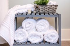 Asciugamani di bagno bianchi lanuginosi rotolati ed impilati fotografia stock