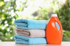 Asciugamani di bagno e detersivo di lavanderia molli sulla tavola fotografia stock