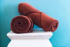 Asciugamani di Brown sulla sedia bianca nella sala Fotografia Stock