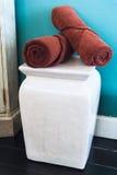 Asciugamani di Brown sulla sedia bianca nella sala Immagini Stock Libere da Diritti