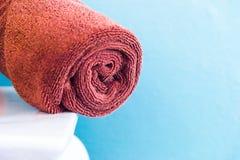 Asciugamani di Brown sulla sedia bianca nella sala Immagine Stock