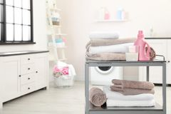 Asciugamani e detersivo di bagno molli sul carretto del metallo contro fondo vago fotografia stock libera da diritti