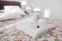 Asciugamani lanuginosi lavati e bianchi e freschi con il fiore sul letto dentro noioso immagini stock libere da diritti
