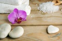 Asciugamani, sali da bagno e pietre bianchi per un massaggio caldo su una tavola di legno Immagine Stock Libera da Diritti
