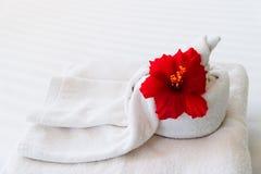 Asciugamano bianco con un fiore su fondo bianco Fotografie Stock Libere da Diritti