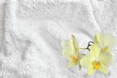 Asciugamano bianco Terry Cloth Texture del cotone ed orchidea gialla fotografia stock