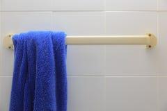 Asciugamano blu che appende su un gancio in bagno Immagine Stock