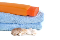 Asciugamano blu con la bottiglia di sunblock e della conchiglia Fotografia Stock