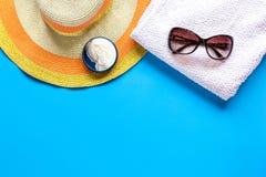 Asciugamano, crema del sole, vetri sullo spazio blu di vista superiore del fondo per testo Fotografia Stock
