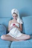 Asciugamano di bagno d'uso della giovane donna con il telefono di globulo rosso Fotografia Stock