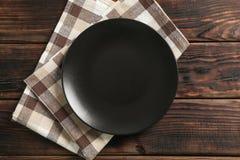 Asciugamano di cucina con il piatto su fondo di legno immagine stock