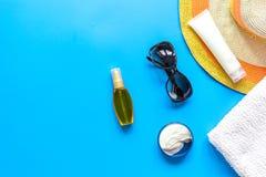 Asciugamano, lozione del sole, vetri sullo spazio blu di vista superiore del fondo per testo Immagini Stock Libere da Diritti
