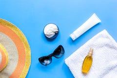 Asciugamano, lozione del sole, vetri sullo spazio blu di vista superiore del fondo per testo Immagine Stock Libera da Diritti