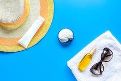 Asciugamano, lozione del sole, vetri sullo spazio blu di vista superiore del fondo per testo Fotografia Stock