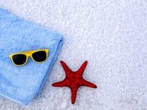Asciugamano, occhiali da sole e stelle marine su un fondo bianco Immagini Stock