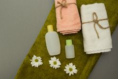 Asciugamano, petrolio e fiori isolati su fondo grigio fotografia stock