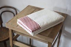 Asciugamano piegato ordinatamente sopra la piccola Tabella di legno immagini stock libere da diritti