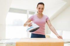 Asciugamano rivestente di ferro della casalinga o della donna da ferro a casa Fotografia Stock Libera da Diritti