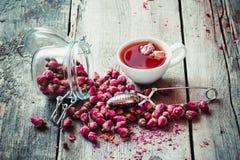 Asciughi i germogli, la tazza di tè, il filtro ed il barattolo rosa di vetro con i boccioli di rosa Fotografie Stock