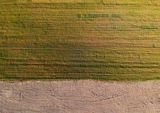 Asciughi il prato cutted con il giacimento della sporcizia, diviso, vista aerea Fotografie Stock