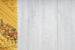 Asciughi la pasta mista con gli spaghetti e il backgroun di legno rustico bianco Immagini Stock Libere da Diritti